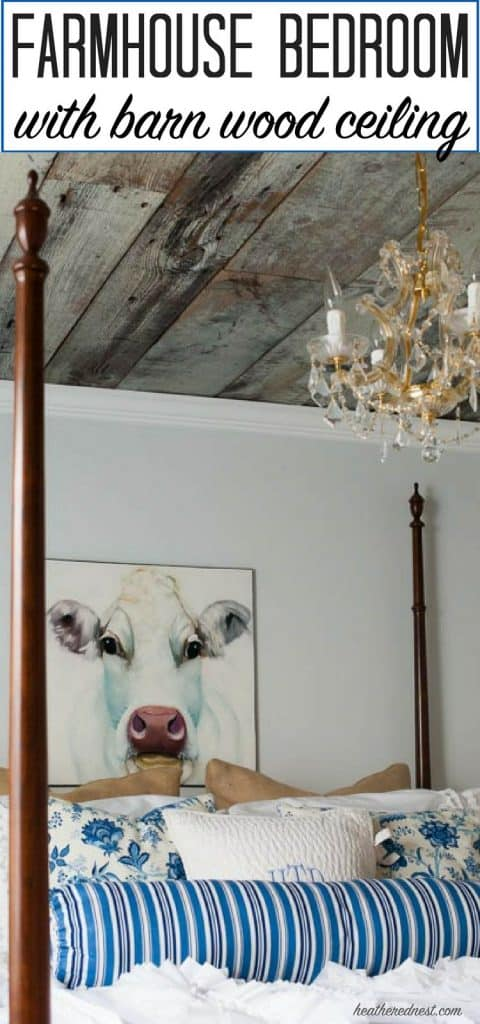barn wood ceiling and a petite gold chandelier over a wood four poster bed and painted portrait of a cow hangs on a wall