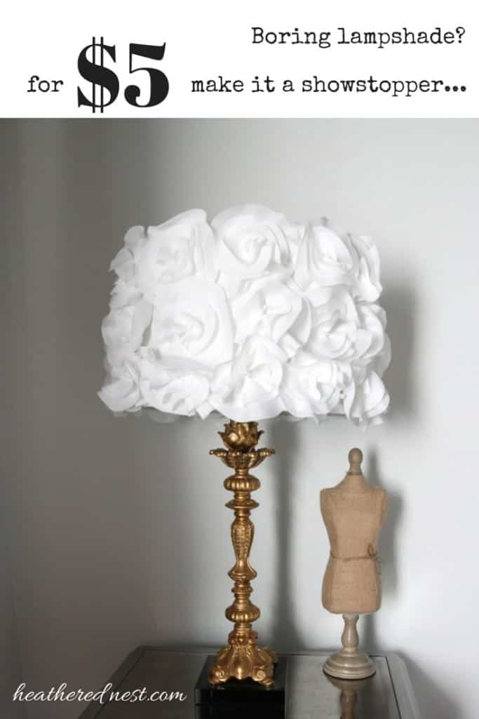"""""""boring lampshade? For $5 make it a showstopper!"""" showing brass candlestick lamp with white fabric floral glam lampshade on a mirror end table"""