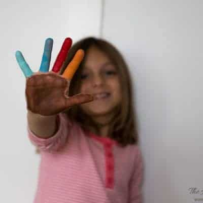 girl showing outstretched hand, palm painted with acrylic paint