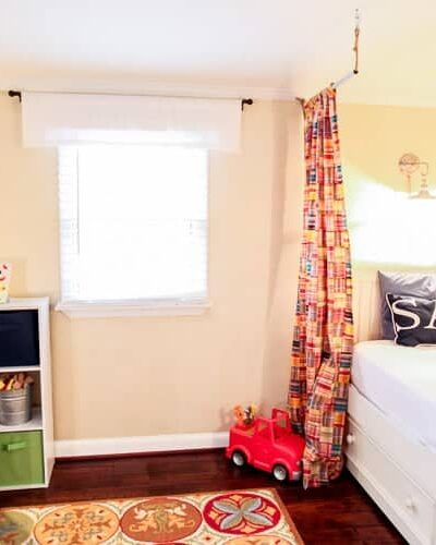 nautical boys room with linen faux painting technique, red craigslist chandelier, hanging model airplanes and madras curtains