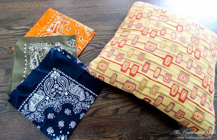 old pillow sitting next to three colorful bandanas from the dollar store: navy, orange and olive green