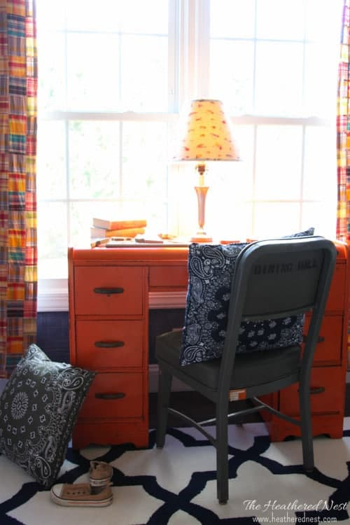 navy bandana pillow on a vintage governement office chair at a bright orange desk in a little boy's bedroom
