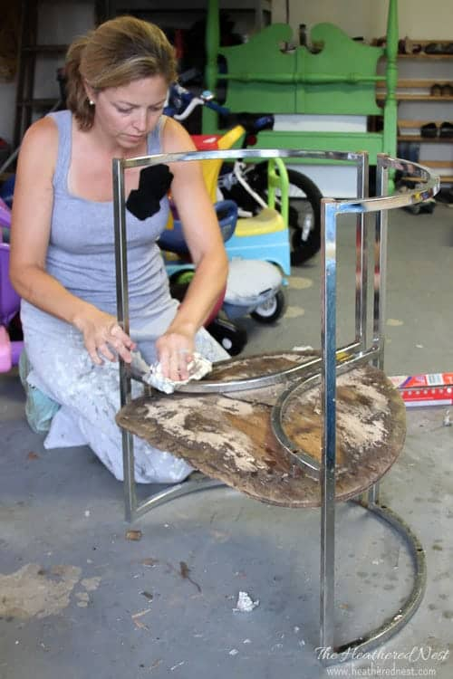 woman in garage working on removing rust from an old chair with metal frame