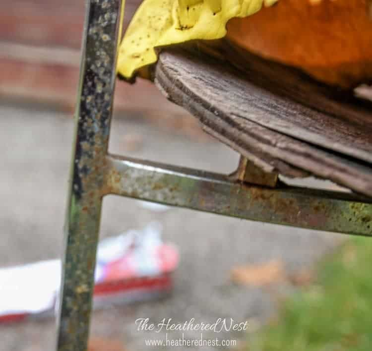 close-up of a vintage chair with rusted chrome frame and lots of wood rot