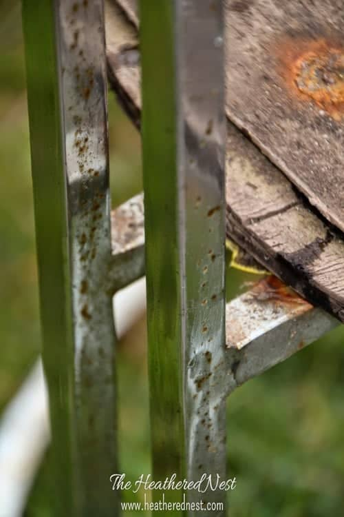 close-up of a vintage chair with rusted chrome frame and wood rot