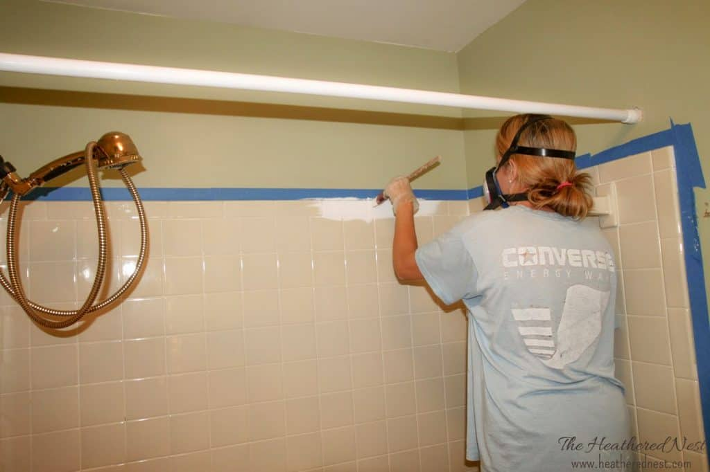 Interested in how tub and tile paint works? We did this project and are sharing tips and tricks as well as how it's held up over the years. Here you can see the first bit of paint being applied to the outdated almond/buff tile.