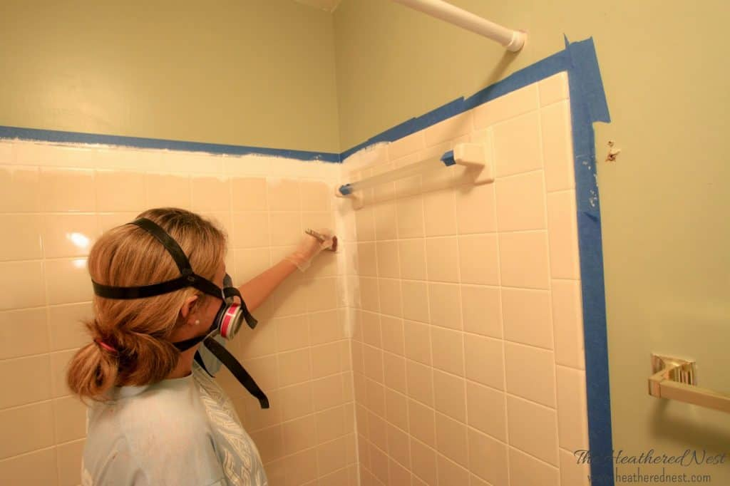 Cutting in the shower and tile corners with a paintbrush prior to rolling on the tub and shower tile paint. Make sure to wear a good respirator mask, as shown.