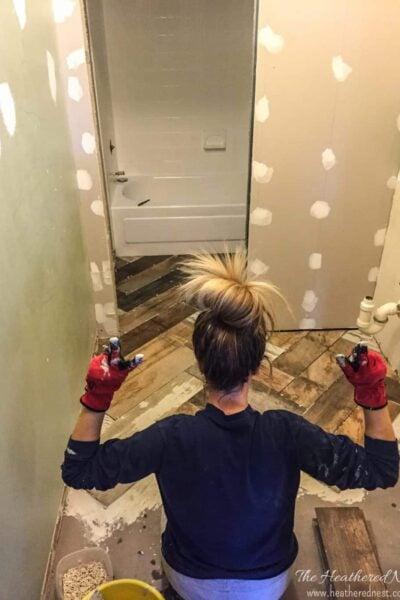 woman tiling bathroom floor