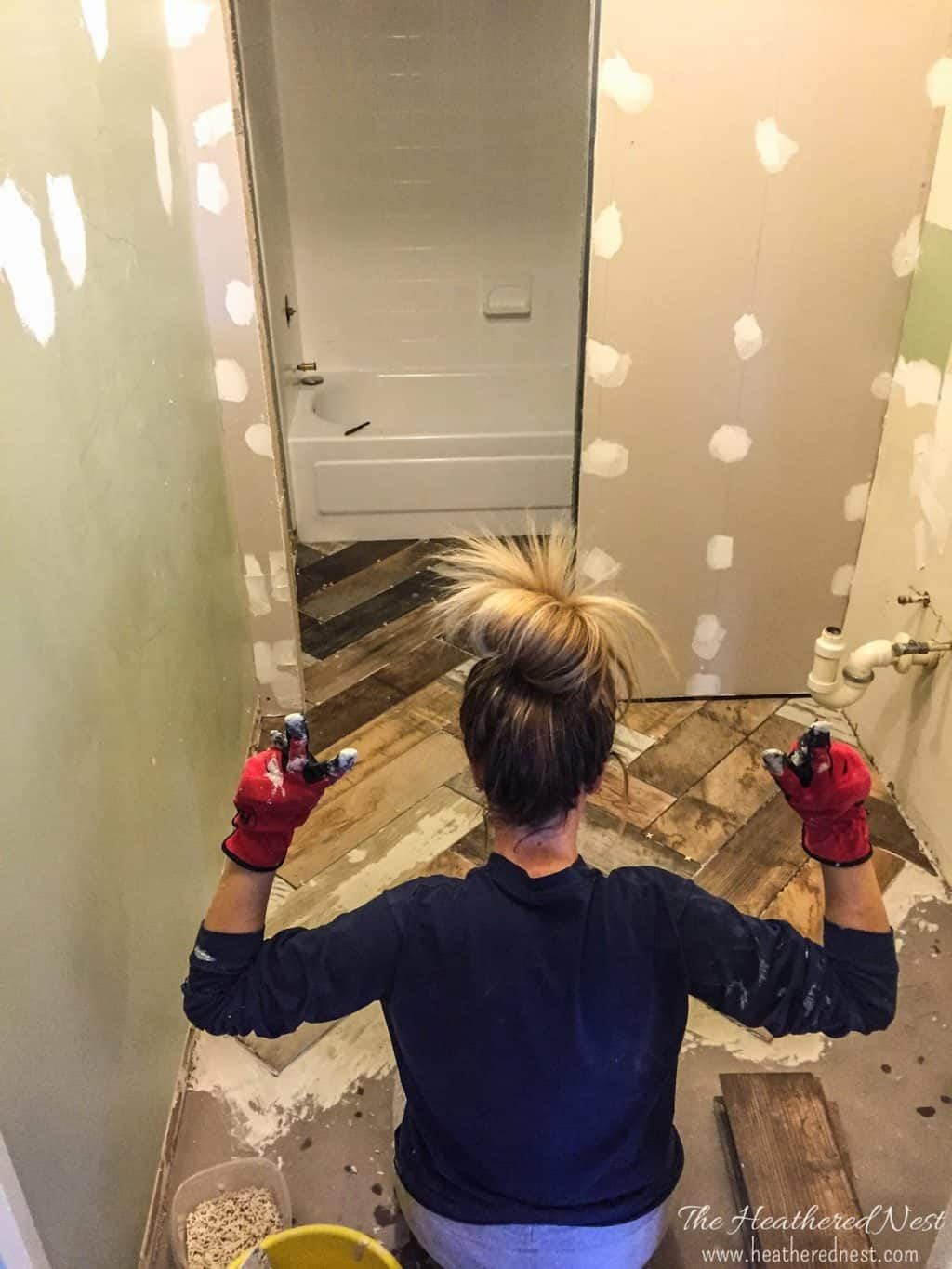 back of woman tiling bathroom floor with workgloves on