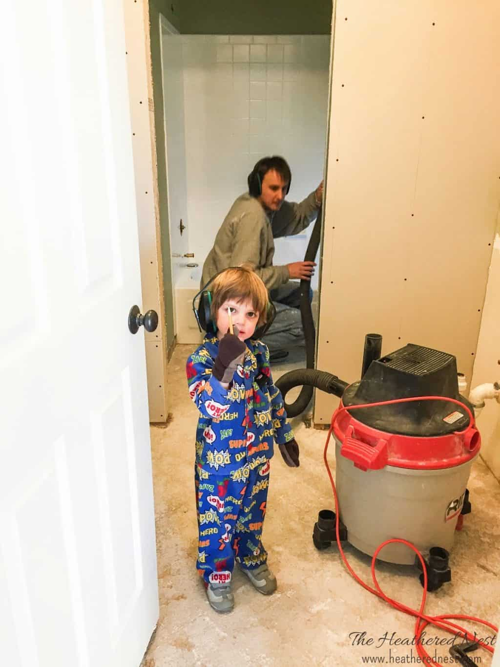 Kids helping (in pajamas) during a DIY bathroom renovation project