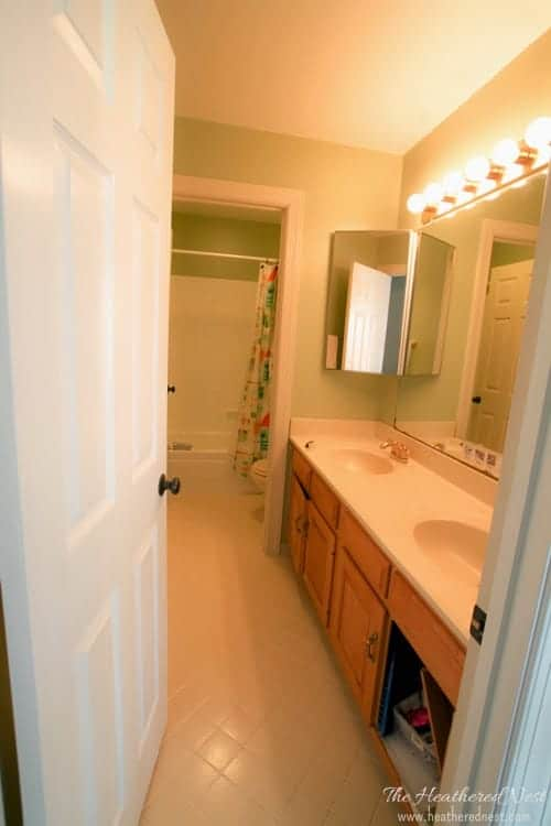 The BEFORE picture of our kids' bathroom - it's dimly lit, drab, and lacking any color! Check out the after picture for some DIY bathroom decor ideas.