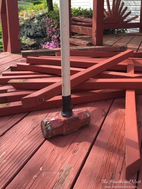 sledgehammer next to some demolished deck railing spindles