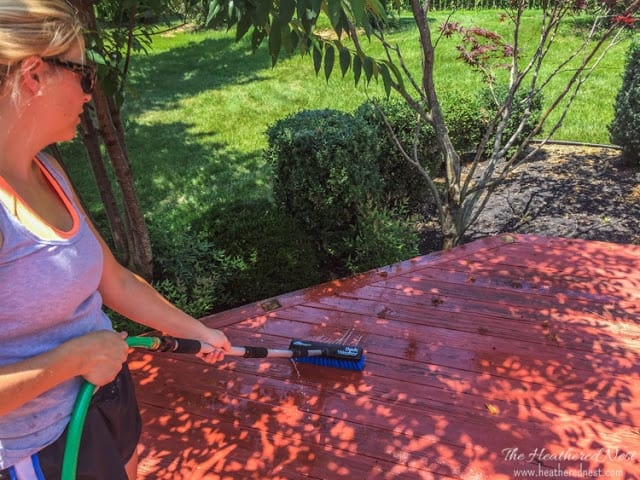 cleaning and scrubbing the deck with a power washer brush tool