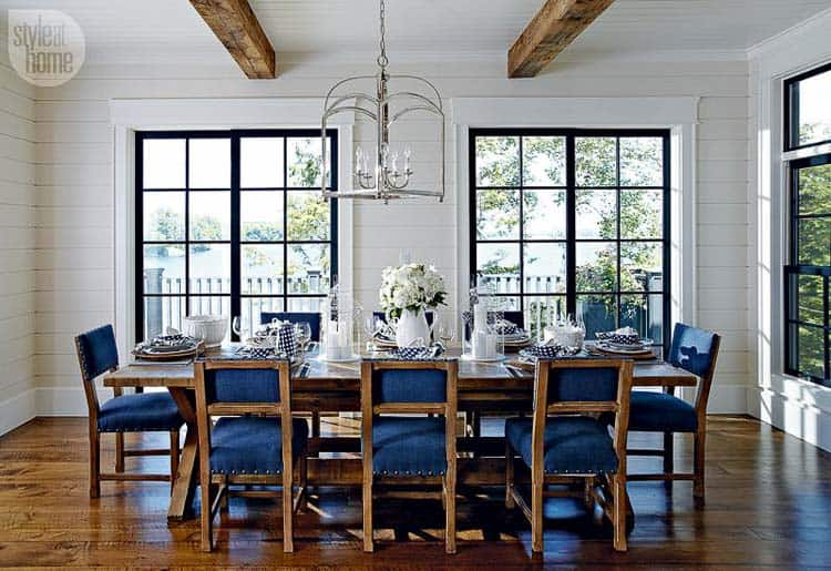 This beautiful and elegant white-wood panelled dining room has rustic faux beams across the top. The dark wood compliments the wooden accents of the denim blue dining chairs, rustic dining table, and beautiful hardwood floors.