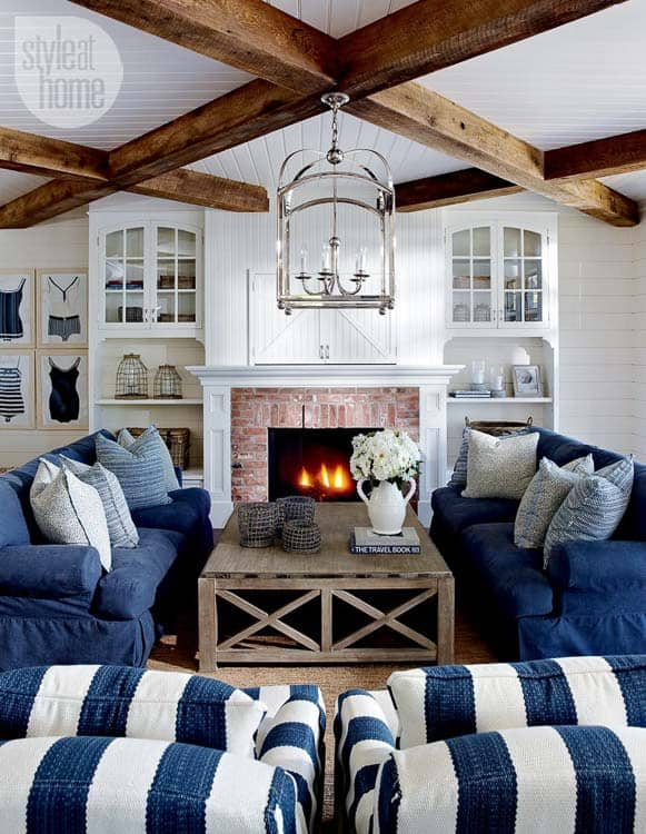 Criss cross patterned wood beams creates a coffered ceiling look in this beachy vibed family room space in blues and whites.
