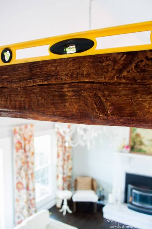Level the faux beam to ensure you get the best look for your new wood beam. Level seen atop the faux wood beam.
