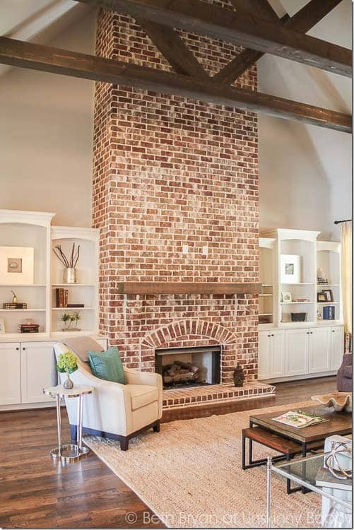 Family room with high vaulted ceilings and multiple wood beams, fireplace with a german smear or possibly limewashed brick look.