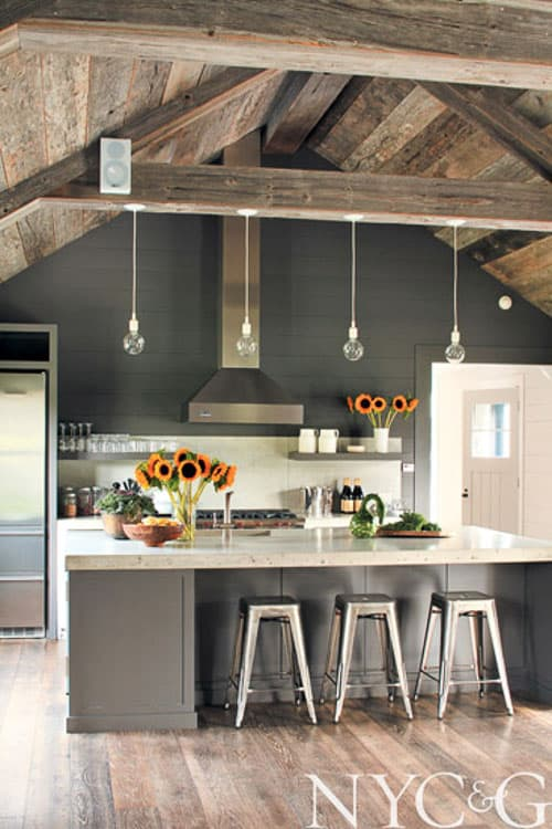This kitchen is the faux beams DREAM! The rustic wooden beams across the ceiling and gorgeous wood panelling along the slanted ceilings bring the perfect amount of sleek country style into this modernized and beautiful kitchen.