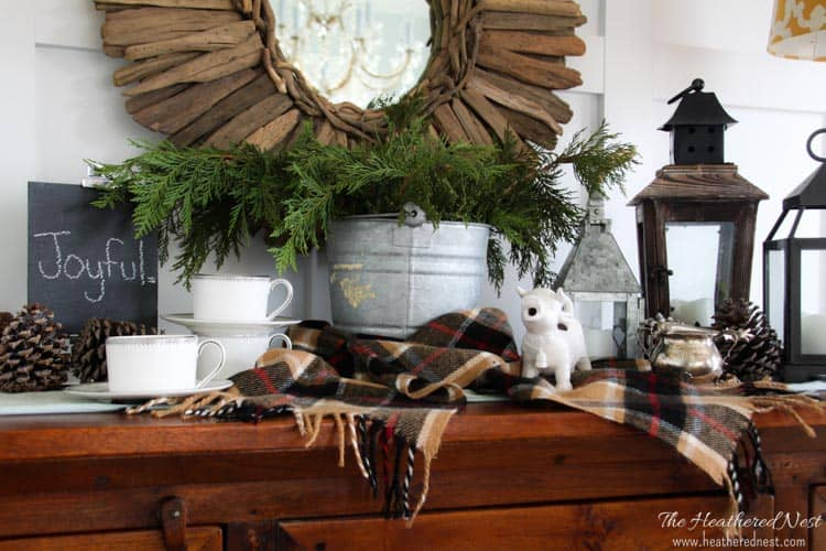 "holiday home tour buffett table with coffee layout, greens, pinecones, chalkboard sign ""joyful"" and driftwood round mirror"