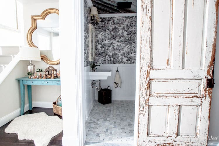 vintage chippy white door on slider revealing black and white toile wallpaper, white wall mounted sink and basketweave marble tile in french country style bathroom with reclaimed barn wood ceiling