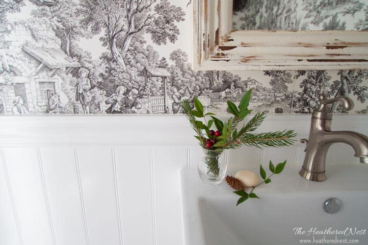 small wintery sprig of pine, greens and berries in french country bathroom for holiday home tour