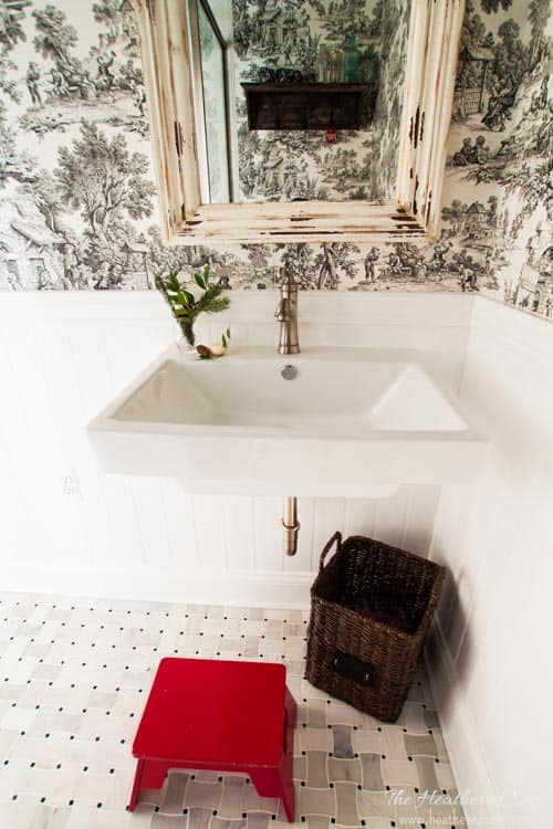 french country bathroom with black and white toile wallpaper, wall mounted sink, beadboard wainscoting, red stool