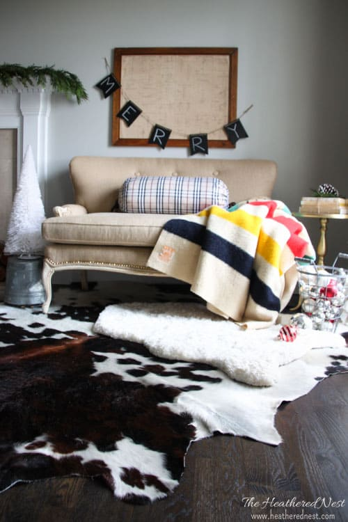 holiday home tour burlap settee with cowhide rug, sheepskin rug, and hudson blanket next to fireplace