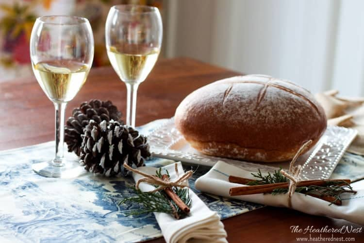 closeup of loaf of bread, two glasses of white wine, pinecones and napkins garnished with pin sprigs and cinnamon sticks