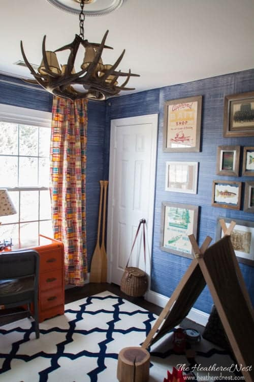 Denim is a classic look be it in fashion or decor. This tutorial teaches you how to do a faux paint technique that looks like denim! Looks like wallpaper that costs hundreds more! Seen here in boys outdoor themed, adventure room with navy and white trellis rug, madras curtains and faux antler chandelier, rustic gallery wall.