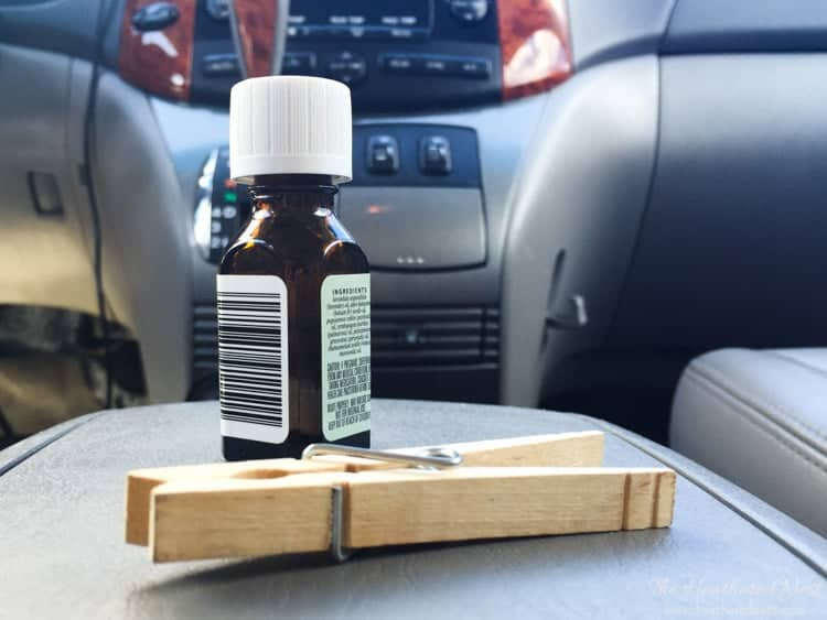 Make an all natural DIY car air freshener in seconds - shown clothespin and small glass bottle of essential oil