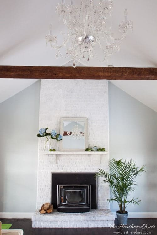 whitewashed brick fireplace with a large wood beam and chandelier