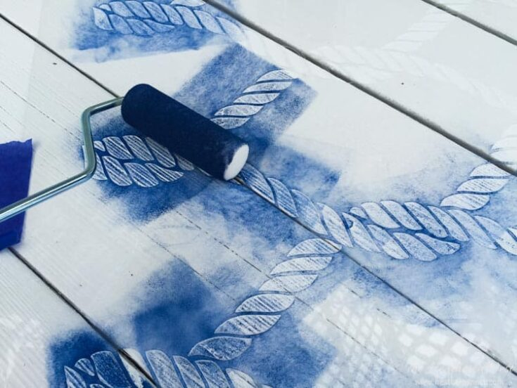 using stencil to paint an outdoor rug with blue paint