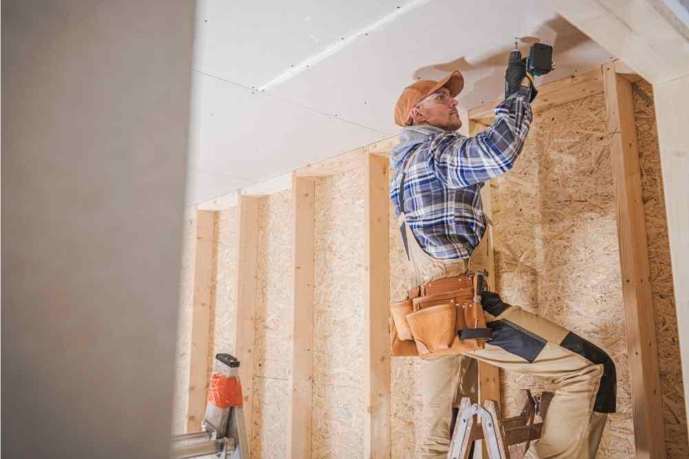 man on ladder screwing sheetrock to ceiling
