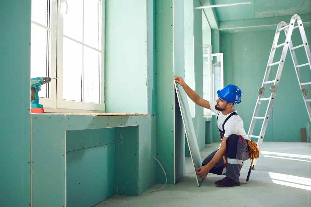 man in blue hard hat hanging drywall