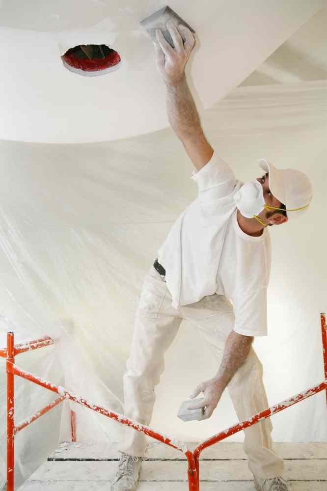 man on scaffold in white shirt and pants sanding new drywall on ceiling