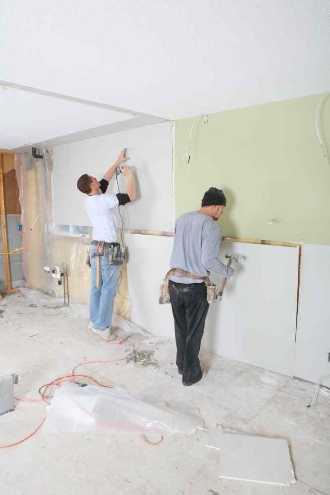two men hanging drywall