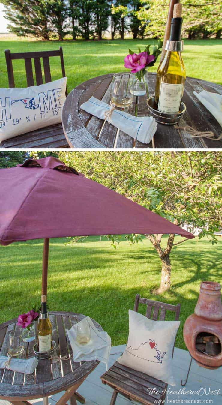 A glass of wine sitting on top of a picnic table, with painted patio umbrella