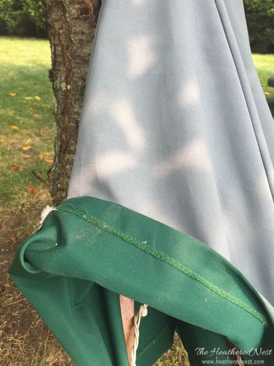 outdoor umbrella leaning against a tree with the bottom end folded up to show how faded it is