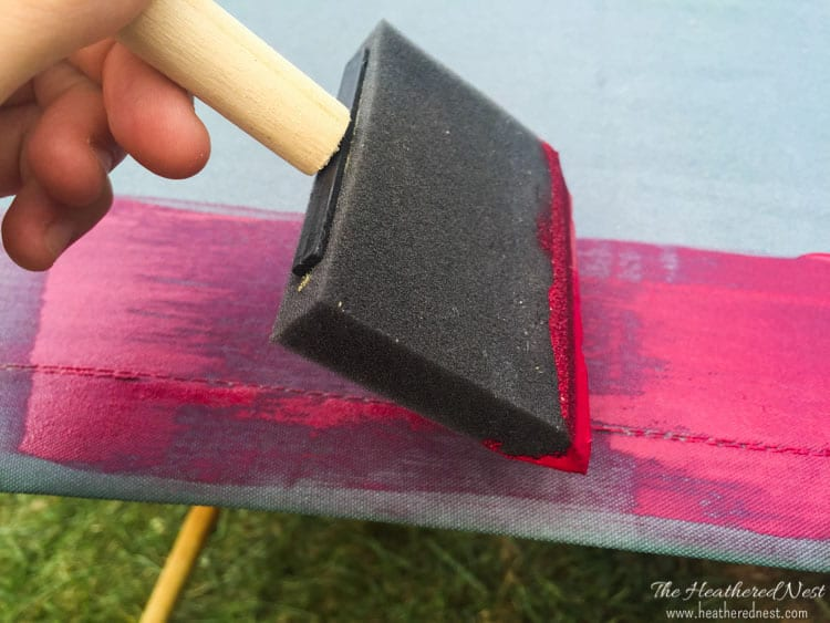 Using a foam brush to even out paint on an outdoor umbrella