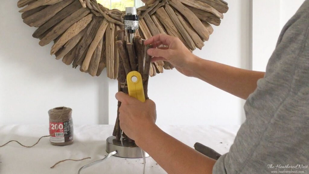 hot gluing jute twine around twigs arranged on the base of a table lamp