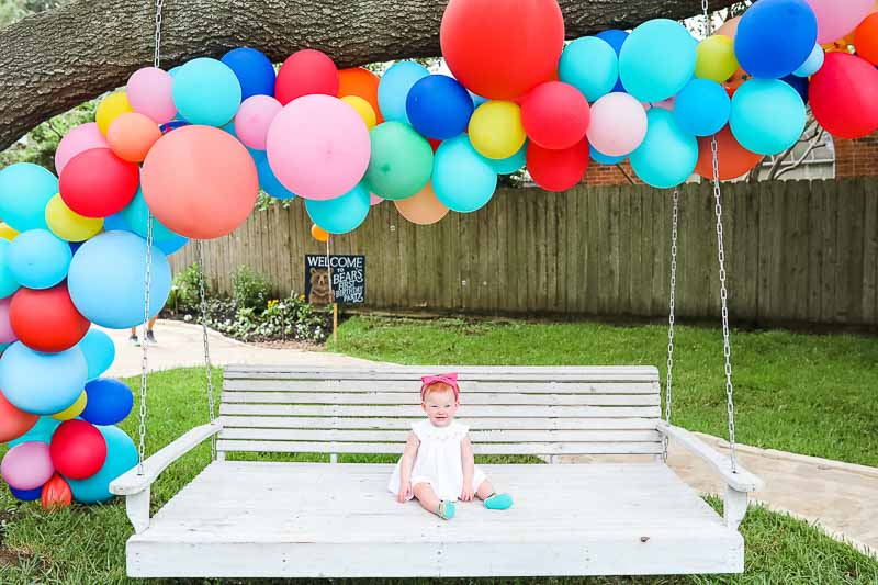 DIY Balloon Garland over white swing with baby girl