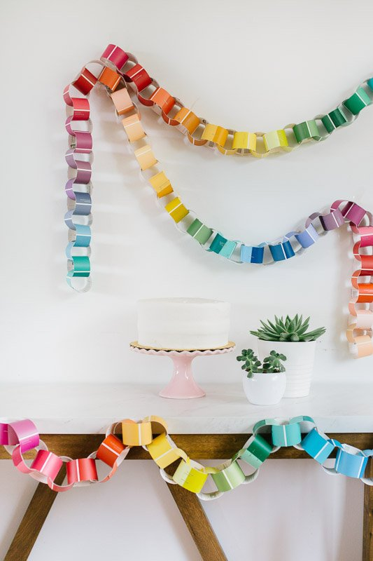 Paint Swatch Chain DIY Garland on a white wall with wood and white bench, birthday cake