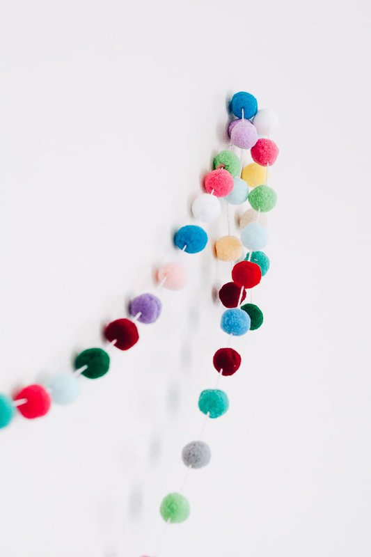 DIY Felt ball or pom pom garland tutorial - garlands shown on white background