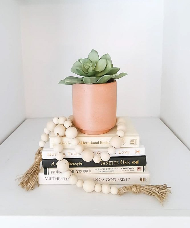 Wood bead garland around a succulent vase and stack of books