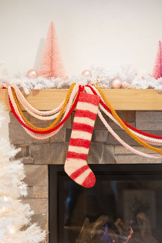 Finger knit DIY Christmas Garland hung on a mantle with red and white striped stocking