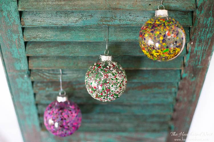 Image of three completed DIY melted crayon ornaments hung on a vintage shutter. Three color combos of this melted crayon art project to include pink and purple, primary colors, and Christmas colors.