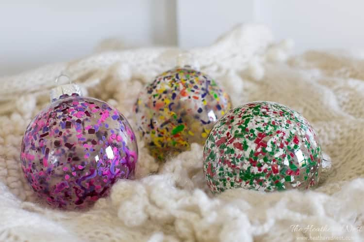 Image of three completed DIY melted crayon ornaments on an ivory winter scarf. Three color combos of this melted crayon art project to include pink and purple, primary colors, and Christmas colors.