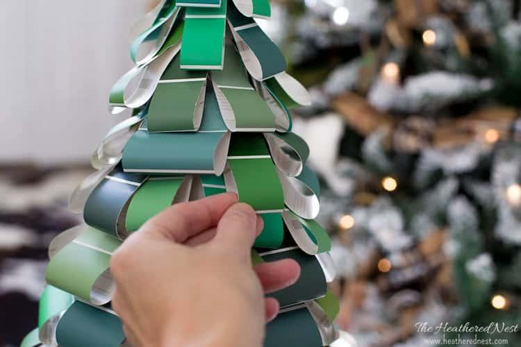 hand touching DIY Christmas tree paint swatch craft!