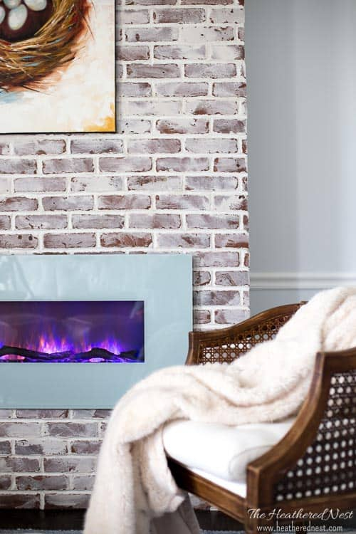 Closeup of brick fireplace with a DIY mortar wash on it to give it a Old World, European type look. Seen in this space with cane chair, electric fireplace.