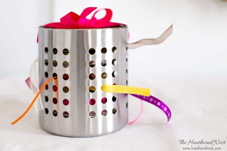 ends of ribbon showing through a steel utensil holder from IKEA as a DIY ribbon storage hack